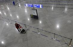 <p>Пассажир, идущий в одиночестве по пустому залу Международного аэропорта Афин, 10 февраля 2010 года. Забастовка греческих государственных служащих привела к приостановке работы аэропортов, части школ и государственных учреждений в среду, угрожая решимости правительства справиться с финансовым кризисом путем строгой бюджетной дисциплины. REUTERS/Yiorgos Karahalis</p>