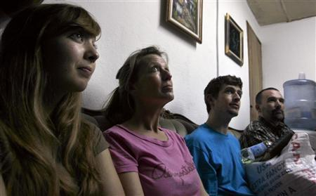 (L-R) Nicole Lankford, Corinna Lankford, Silas Thompson and Paul Thompson, four of the 10 U.S. missionaries accused of kidnapping children, sit inside the judge's office at the Judicial Police station in Port-au-Prince February 10, 2010. REUTERS/Ivan Alvarado