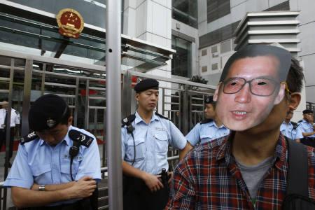 A pro-democracy protester wears a mask of jailed Chinese dissident Liu Xiaobo as police watch during a demonstration outside a Chinese liaison office in Hong Kong February 11, 2010. REUTERS/Bobby Yip
