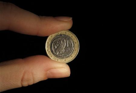 A woman holds a Greek euro coin in Athens February 10, 2010. REUTERS/Yiorgos Karahalis