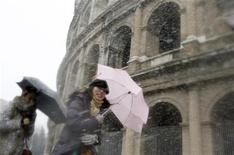 <p>Turiste giapponesi sotto la neve di fronte al Colosseo, Roma, 12 febbraio 2010. REUTERS/Alessandro Bianchi</p>