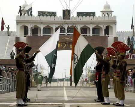 Soldiers of the Border Security Force of India (BSF) (R) and Pakistani Rangers hold their respective flags during the ''Beating the Retreat'' ceremony, a daily ritual, at Indian and Pakistani joint check post at Wagah border on the outskirts of Amritsar in this December 17, 2007 file photo. REUTERS/Munish Sharma/Files