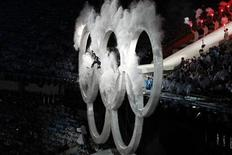 <p>A snowboarder soars through the centre ring of the Olympic Rings during the opening ceremony of the Vancouver 2010 Winter Olympics, February 12, 2010. REUTERS/Gary Hershorn</p>