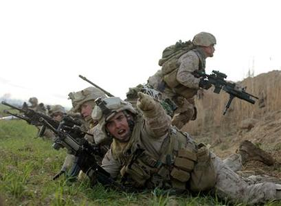 A U.S. Marine from Bravo Company of 1st Battalion, 6th Marines, gestures during a gun battle in the town of Marjah, in Nad Ali district of Helmand province, February 13, 2010. REUTERS/Goran Tomasevic