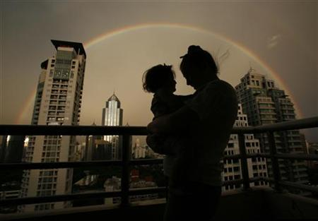 A mother and child are silhouetted by a rainbow arching over Bangkok's skyline on May 27, 2007. REUTERS/Adrees Latif