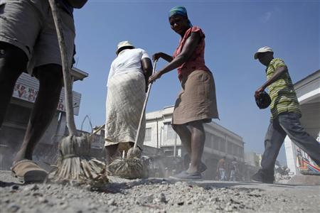 A woman sweeps a busy street in downtown Port-au-Prince, February 16, 2010. REUTERS/Carlos Barria