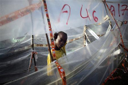 A boy stands inside a makeshift tent after heavy rain during the night in Cite Soleil, Port-au-Prince February 18, 2010. REUTERS/Carlos Barria