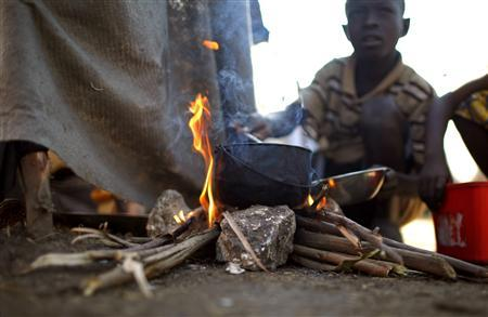 A boy cooks at a makeshift campsite in Cite Soleil, Port-au-Prince February 22, 2010. REUTERS/Carlos Barria