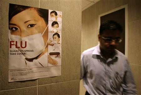 A man walks past a poster advising people to wear a mask if they have flu symptoms in Singapore May 19, 2009. REUTERS/Vivek Prakash