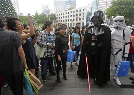 Onlookers take photos of people dressed as Star Wars characters as they walk down a sidewalk on Orchard Road in Singapore December 20, 2009. Some 30 characters, including a Darth Vader and storm troopers, walked around the popular shopping district as part of a publicity stunt for Adidas. REUTERS/Vivek Prakash