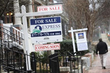 A man walks past signs marking houses for sale in Washington, January 24, 2010. REUTERS/Jonathan Ernst