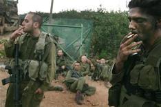 <p>Израильские солдаты курят на израильско-ливанской границе 1 августа 2006 года. Коэффициент интеллекта (IQ) курильщиков ниже, чем у некурящих людей, и чем больше человек курит, тем ниже его IQ, следует из данных исследования, проведенного среди 20.000 израильских призывников. REUTERS/Kai Pfaffenbach</p>