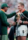 <p>South African President Nelson Mandela (L) shakes hands with Springok captain Francois Pienaar after their team defeated New Zealand in the Rugby World Cup final in Johannesburg in this June 24, 1995 file photo. REUTERS/Mark Baker/Files</p>