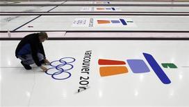 <p>Рабочий проверяет логотип Олимпиады-2010 в Ванкувере на дорожке для керлинга 9 февраля 2010 года. REUTERS/Todd Korol</p>