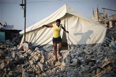<p>A woman exits a tent that was erected over the remains of a house at Fort National neighborhood in Port-au-Prince, Haiti February 24, 2010. REUTERS/Carlos Barria</p>