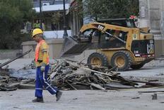 <p>Рабочий убирает обломки в столице Чили Сантьяго после землетрясения 27 февраля 2010 года. Мощное землетрясения в Чили унесло жизни минимум 47 человек, сказала президент страны Мишель Бачелет, не исключив роста числа жертв в дальнейшем. REUTERS/Victor Ruiz Caballero</p>