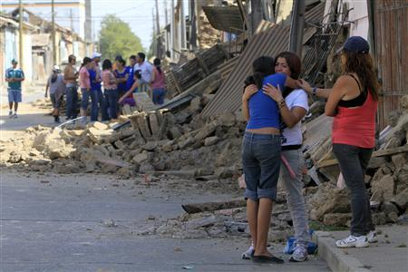 Women cry next to a destroyed building in Talca, some 300 km (186 miles) south of Santiago, February 27, 2010. REUTERS/Victor Ruiz Caballero