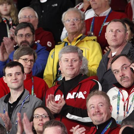 Canada's Prime Minister Stephen Harper (C, wearing Canada sweater) and Sweden's King Carl XVI Gustaf (yellow jacket) attend the Women's Gold medal game in curling at the Vancouver 2010 Winter Olympics, February 26, 2010. REUTERS/Andy Clark