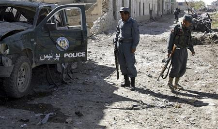 An Afghan policeman (L) looks at a damaged police truck after a blast in Kandahar March 1, 2010. REUTERS/Naadem