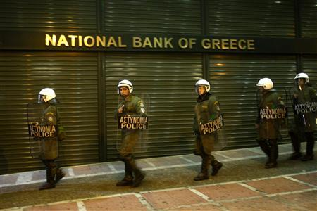 Riot policemen secure a branch of the National Bank of Greece during an anti-government rally in Athens, March 4, 2010. REUTERS/John Kolesidis