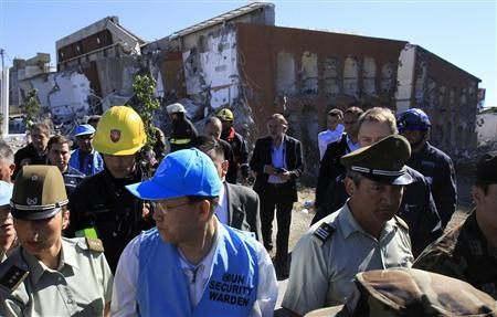 UN Secretary-General Ban Ki-moon (C) visits the Alto Rio apartment building that collapsed during the earthquake, in Concepcion March 6, 2010. REUTERS/Victor Ruiz Caballero