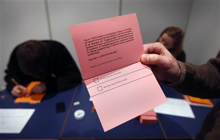An election official holds a ballot paper for a referendum in Reykjavik March 6, 2010. REUTERS/Bob Strong