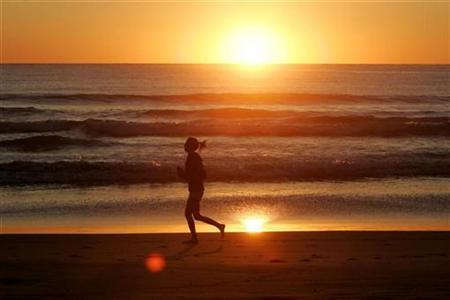 A jogger runs along the shore of Manly Beach in Sydney September 1, 2008. REUTERS/Will Burgess