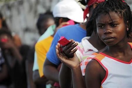 A woman holds a food ticket as she waits in line for food distributed by various relief agencies in Cite Soleil, Port-au-Prince February 18, 2010. REUTERS/Carlos Barria