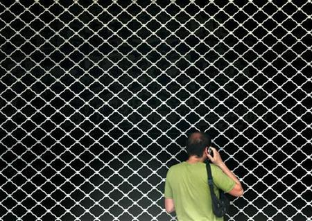A man speaks on the phone as he stands in front of a closed metro station during a 24 hour nationwide strike in Athens July 26, 2005. REUTERS/Yiorgos Karahalis