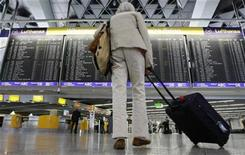 <p>A passenger stands in front of the main board in the departure hall at Frankfurt airport July 28, 2008. REUTERS/Alex Grimm</p>