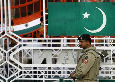 A Pakistani Ranger stands near the Pakistani flag and Indian flag (L) during a daily parade at the Pakistan-India joint check post at Wagah border, on the outskirts of Lahore February 26, 2010.  REUTERS/Mohsin Raza/Files