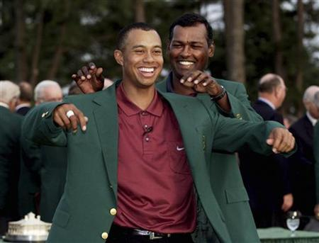 Tiger Woods of the U.S. smiles as he receives the traditional green jacket from former winner Vijay Singh of Fiji to signify his win of the Masters at Augusta National Golf Club in this April 8, 2001 file photo. REUTERS/Kevin Lamarque