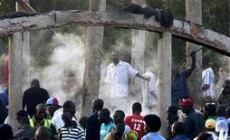 <p>Местные жители разбирают завалы на месте сгоревшего мавзолея королей в пригороде Кампалы 17 марта 2010 года. Огонь уничтожил большую часть захоронения королей Буганды в Касуби, входящего в список Всемирного наследия ЮНЕСКО, сообщила полиция в среду. REUTERS/James Akena</p>