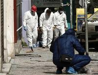 """<p>Полицейские осматривают место взрыва в Афинах 19 марта 2010 года. Самодельное взрывное устройство взорвалось в центре Афин в здании, где находится офис ультраправой организации """"Хриси Авги"""" (""""Золотой рассвет""""), сообщила полиция. REUTERS/John Kolesidis</p>"""