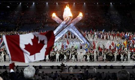 Gordon Campbell, the Premier of British Columbia (L), waves a Canadian flag during the closing ceremony of the Vancouver 2010 Winter Olympics, February 28, 2010. REUTERS/Jim Young