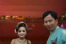 <p>Жених и невеста приветствуют гостей недалеко от Пномпеня 15 февраля 2009 года. Власти Камбоджи временно запретили выходить женщинам замуж за жителей Южной Кореи из-за случаев торговли людьми. REUTERS/Adrees Latif</p>
