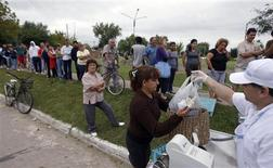 <p>People line up to buy cheap fish at a park in Ituzaingo, on the outskirts of Buenos Aires March 20, 2010. REUTERS/Marcos Brindicci</p>