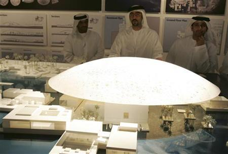 Emirati citizens look at a model of the Louvre Abu Dhabi during the signing of a cultural exchange agreement in Abu Dhabi March 6, 2007. REUTERS/Osayd Hasan