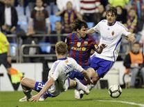 <p>Messi é marcado por dois jogadores do Zaragoza. Os jogadores de futebol precisam conquistar uma Copa do Mundo para que possam ser considerados uma lenda do esporte, disse o atacante argentino Lionel Messi, eleito o melhor de mundo pela Fifa no ano passado.21/03/2010.REUTERS/Luis Correas</p>