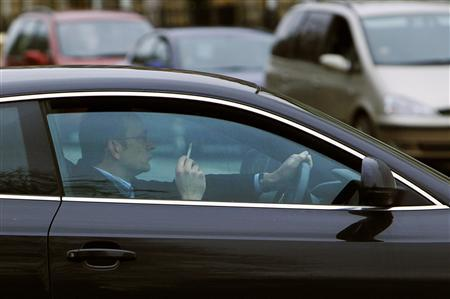A driver sits in his car with a lit cigarette at traffic lights in Edinburgh, Scotland March 24, 2010. REUTERS/David Moir