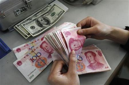 An employee counts yuan banknotes next to U.S. dollar banknotes at a branch of Bank of China in Changzhi, Shanxi province, March 9, 2010. REUTERS/Stringer