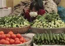<p>A vendor eats her lunch at a vegetable stall at a market in Nanjing, Jiangsu province, December 11, 2008. REUTERS/Sean Yong</p>