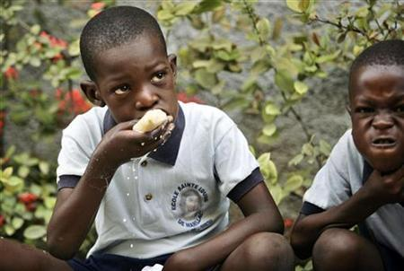 A child eats breakfast before the beginning of a class day at a provisional school in the Cite-Soleil slum of Port-au-Prince March 18, 2010. REUTERS/Eduardo Munoz