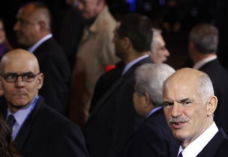 Greek Prime Minister George Papandreou (R) leaves the European council headquarters at the end of the first day of a EU leaders summit in Brussels March 25, 2010. Thursday.REUTERS/Yves Herman