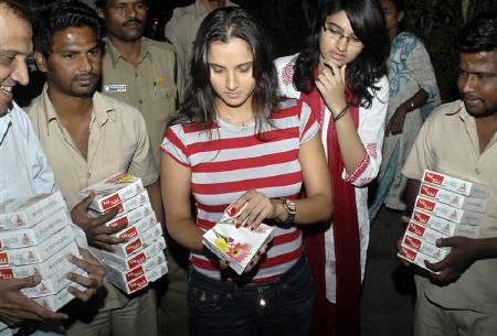 India's tennis player Sania Mirza (C) opens a box of sweets to distribute among the media outside her residence in Hyderabad March 30, 2010.  Pakistani cricketer Shoaib Malik and Mirza, two of South Asia's best known sports personalities, are to marry in April, the players said on Tuesday. REUTERS/Krishnendu Halder