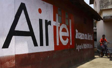 A boy rides his bicycle past an advertisement of Bharti Airtel in Kochi March 31, 2010. REUTERS/Sivaram V