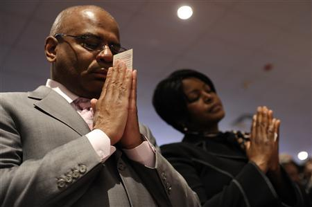 Parishioners hold their offering envelopes and say a pray of thanks for their life's blessings during a Sunday morning worship service at Ebenezer AME Church in Fort Washington, Maryland, March 28, 2010. REUTERS/Jonathan Ernst