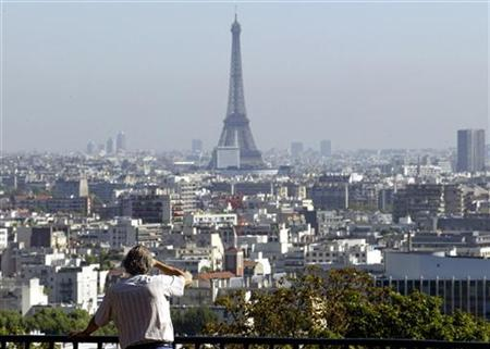 A passer-by looks over Paris through a pollution haze in Saint Cloud, Paris suburb, September 20, 2003. REUTERS/Philippe Wojazer