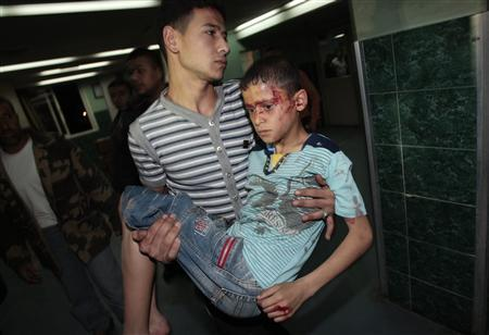 A wounded Palestinian boy is carried into Al-Shifa hospital following Israeli air strikes in Gaza April 2, 2010. REUTERS/Ismail Zaydah