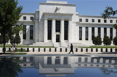 The U.S. Federal Reserve is reflected in a car as a security officer patrols the front of the building in Washington, June 24, 2009. REUTERS/Jim Young